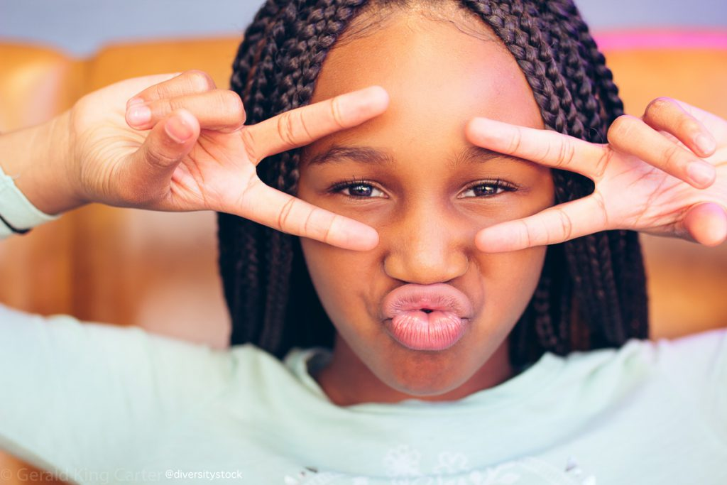 Young black girl with peace sign over her eyes